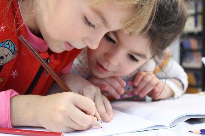Lapset kirjoittavat vihkoon.