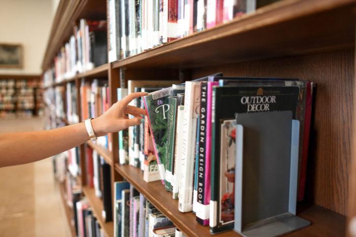 Nainen ottaa kirjan lirjaston kirjahyllystä.
