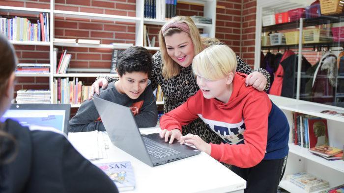 Opettaja ja oppilaat katsovat yhdessä tehtäviä tietokoneella.