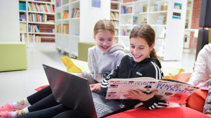 Kouluikäiset tytöt lukevat kirjoja yhdessä.