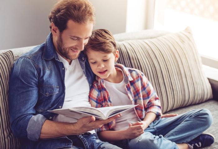 Isä lukee pojan kanssa kirjaa sohvalla.