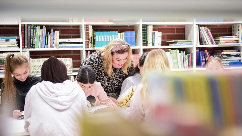 Opettaja tekee tehtäviä yhdessä oppilaiden kanssa luokkahuoneessa