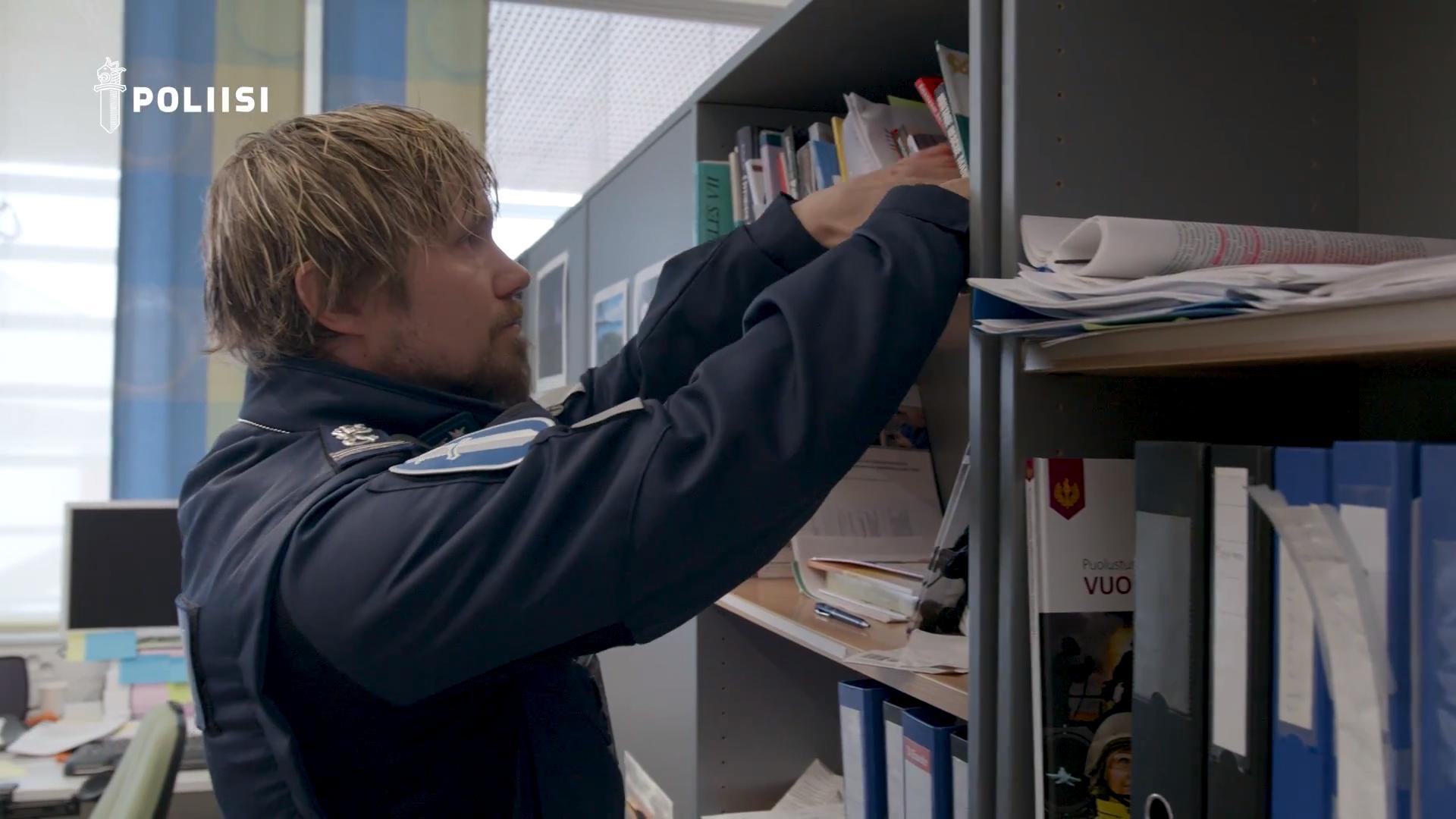 Kuvakaappaus polamk lukee -videosta: poliisi järjestelee kirjahyllyä