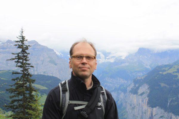 Lehtori Reijo Kupiainen seisoo vuoristomaisemassa