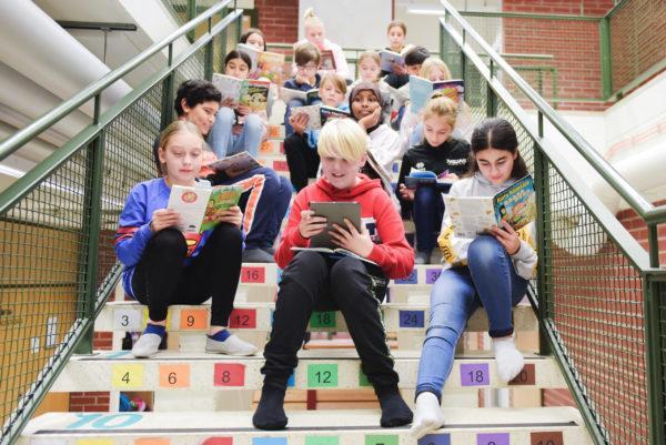 Lapset lukevat portailla ryhmässä. Kuva: Eeva Murtolahti