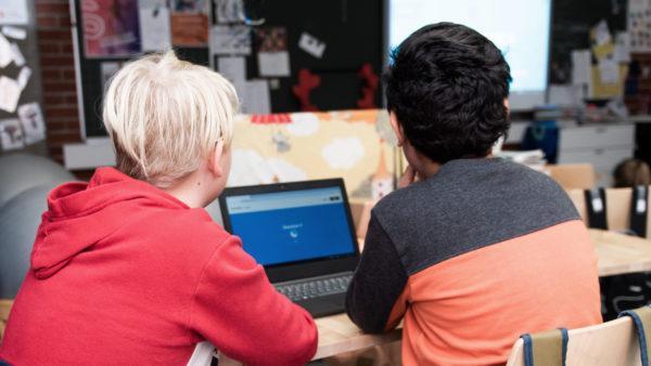 Kaksi lasta katsoo tietokoneen ruutua