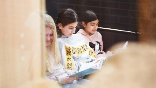 Kolme tyttöä lukemassa